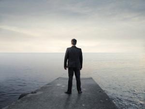 man thinking near water