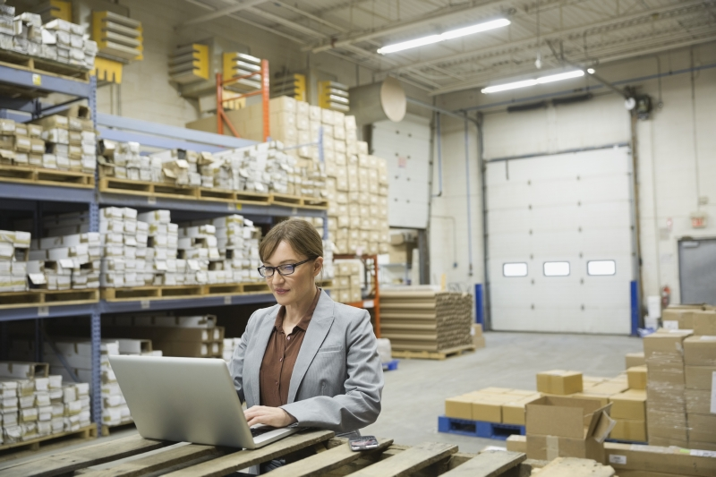 woman at laptop in warehouse