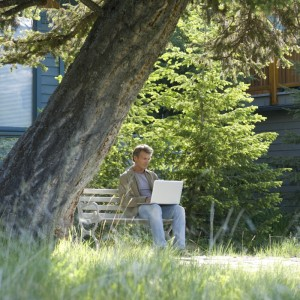 man using laptop under tree