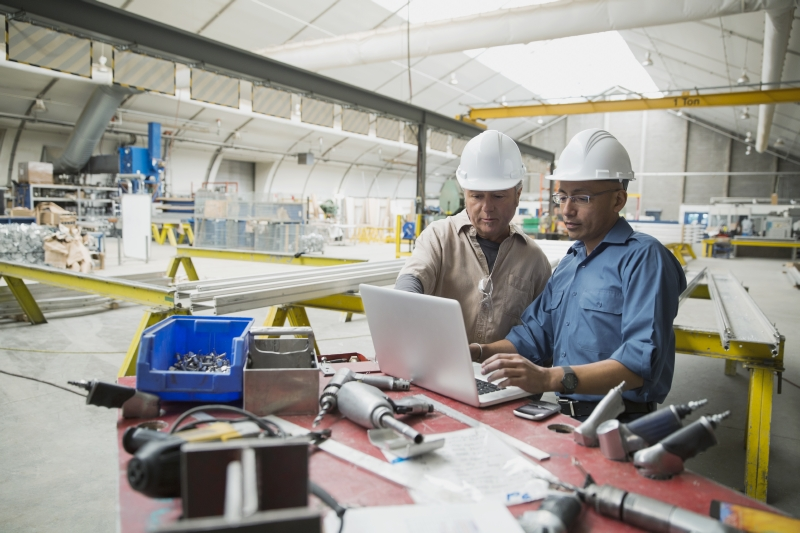 factory workers checking data on laptop