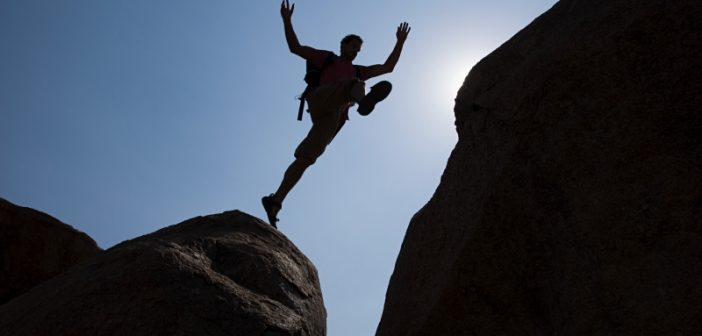 man jumping chasm represents the divide between data management and analytics