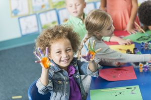 preschool girl gets her hands dirty with fingerpainting, similar to adults doing self-service data preparation