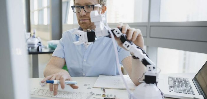 Man working with robotic arm working together with data as a decision maker
