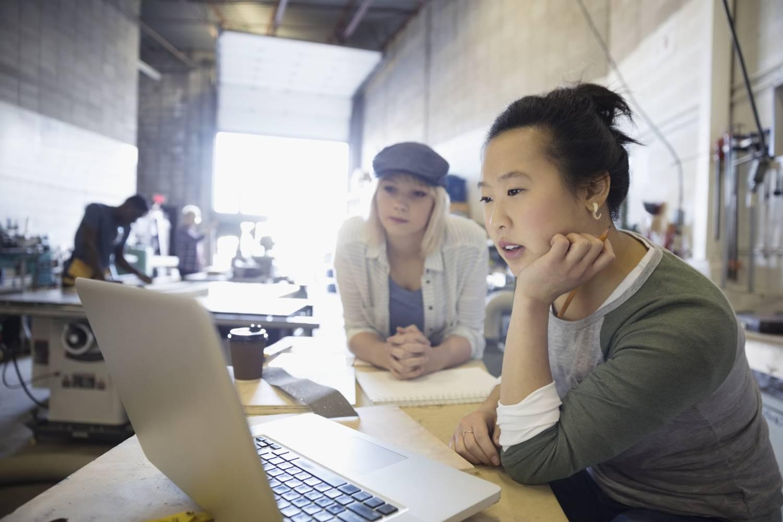 Businesswomen studying laptop, considering value of data literacy