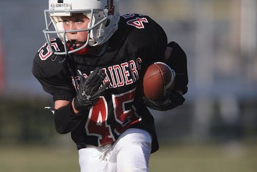 Boy playing football (photo compliments of Pexels)