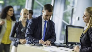 Man signing unemployment check represents the role data management protocols play in enforcing legislation