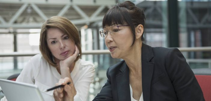 Business women discuss data tagging best practices for their organization