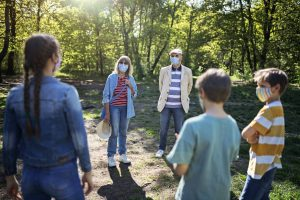 Family meets outdoors and socially distanced with masks during coronavirus