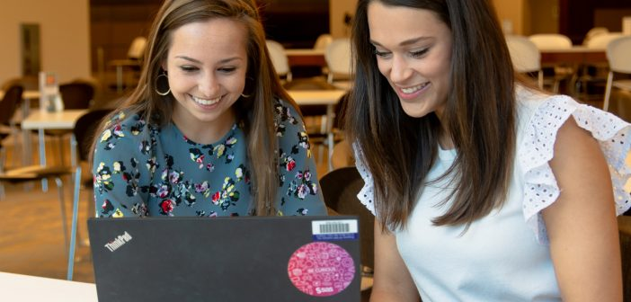 Two SAS interns working at a computer.