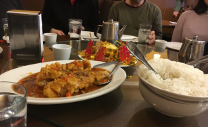 Chinese food dish with a side of rice