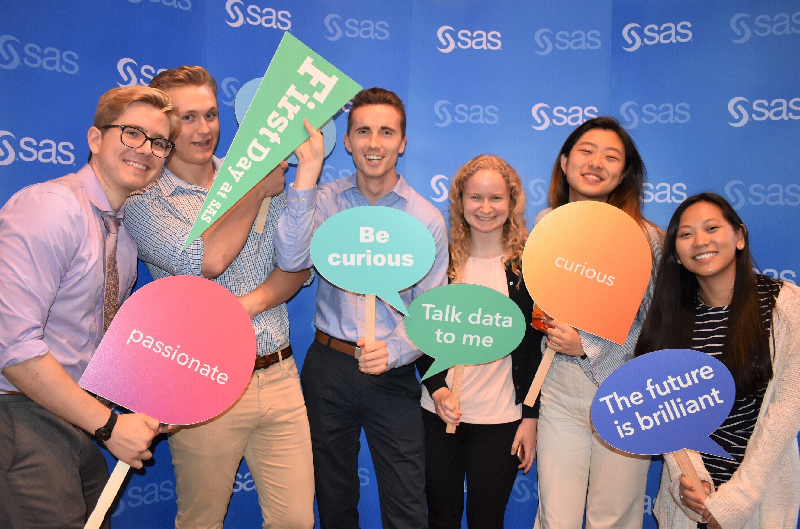 A group of SAS interns pose with signs on their first day.