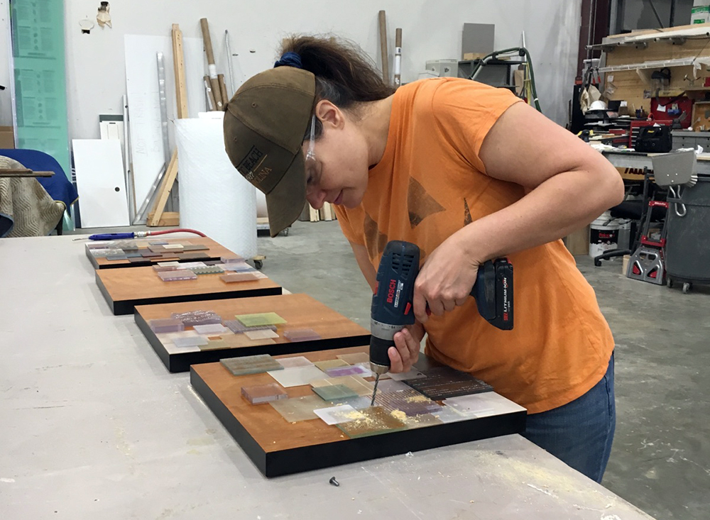 "Juliana Craig drills acrylic squares onto wood to create her art piece ""Array."""