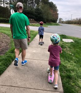 A father walks with his kids as they scooter on a sidewalk