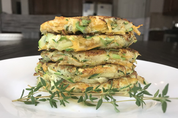 side view of a stack of 5 zucchini butternut squash pancakes with a sprig of thyme