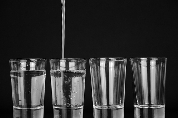 four clear glass being filled with water