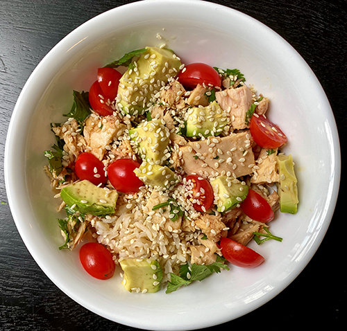 tuna, rice, avocado tomatoes and rice topped with sesame seeds in a white bowl