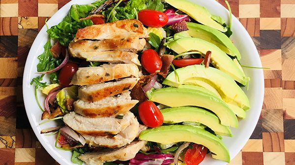 salad of mixed greens topped with slices of grilled chicken, avocados and cherry tomatoes