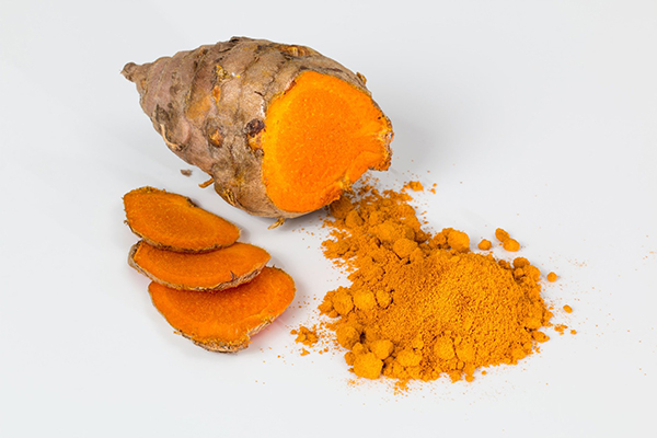 a piece of fresh turmeric with sliced and ground turmeric beside it