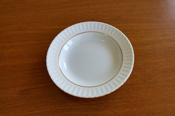 empty white plate on wooden surface