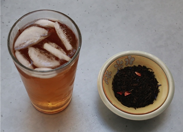 iced tea in a glass and a small bowl with tea leaves