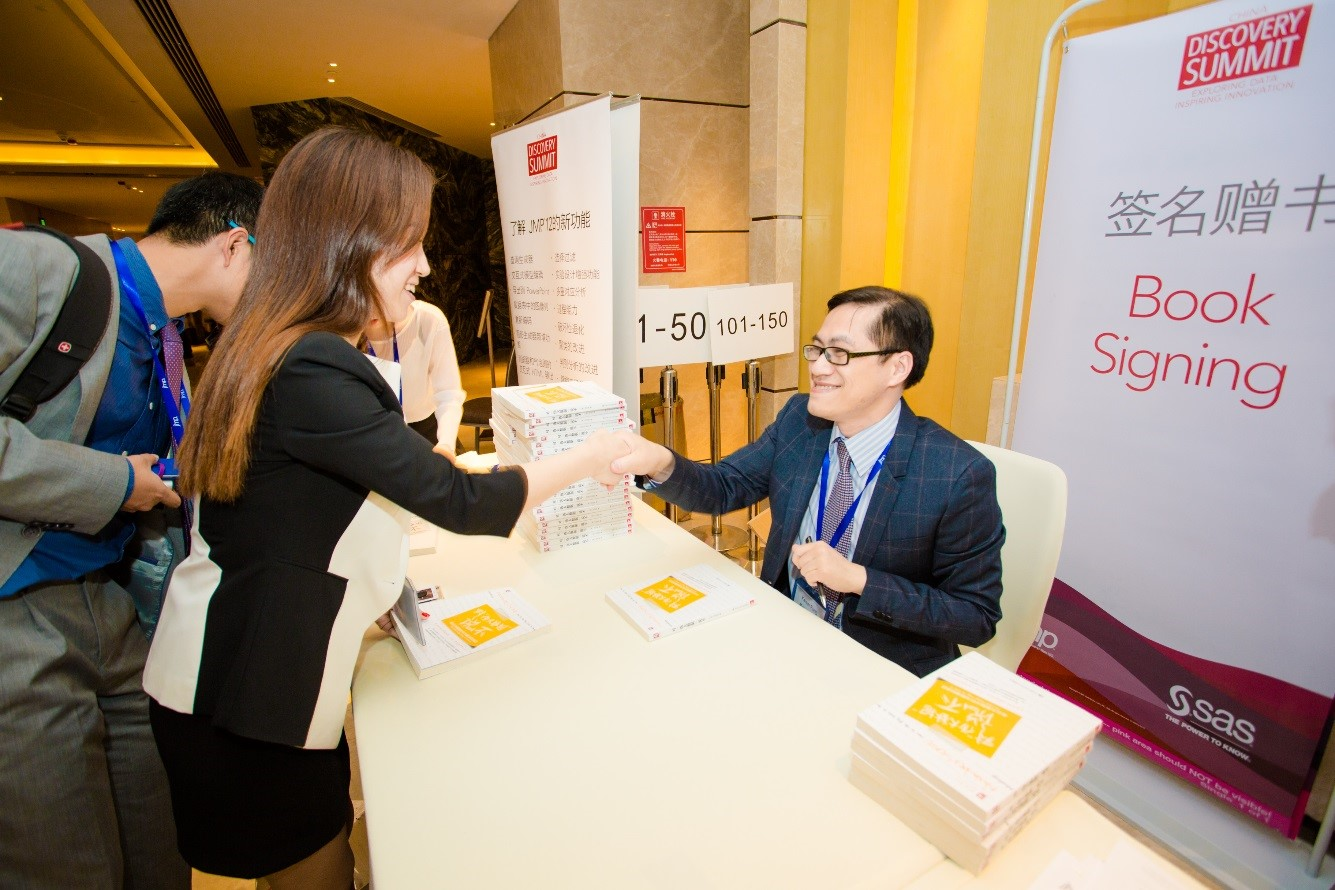 Kaiser Fung signs copies of his book during the one-day analytics conference