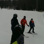 Ed is skiing with the help of Adaptive Sports Center instructors