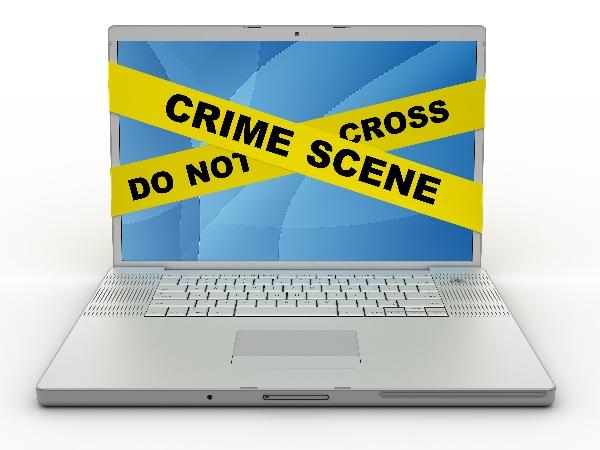crime scene tape over laptop