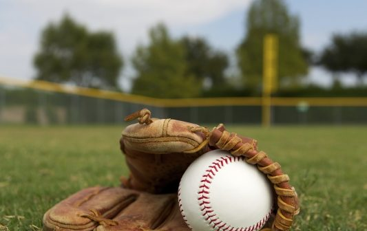 baseball in glove lying on field