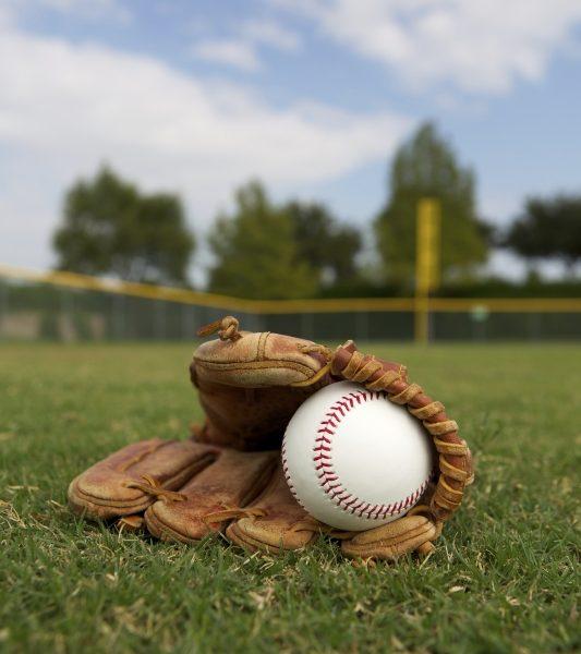 baseball in glove lying on field