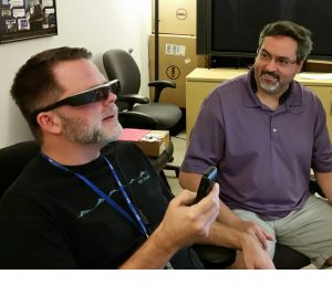 Matthew Horn assists John Anderson, Senior Software Developer, with augmented reality glasses from Epson, the Moverio BT-200.