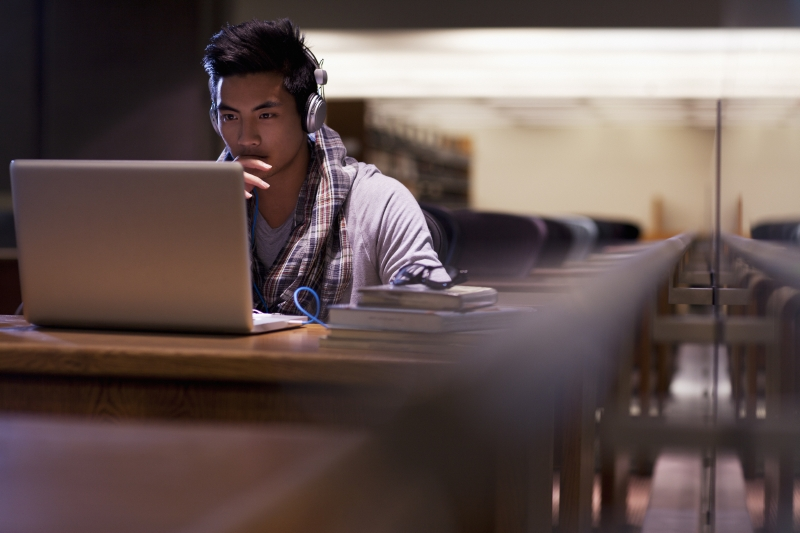 young man at laptop in library