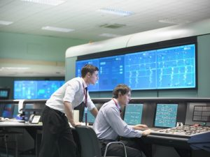 Two men viewing large monitors in a utility control room