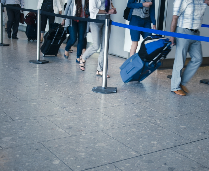 travelers pulling suitcases through an airport security line