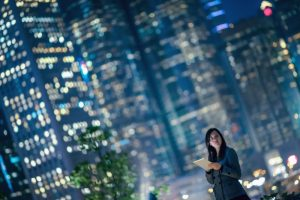 modern woman in front of tall, modern buildings