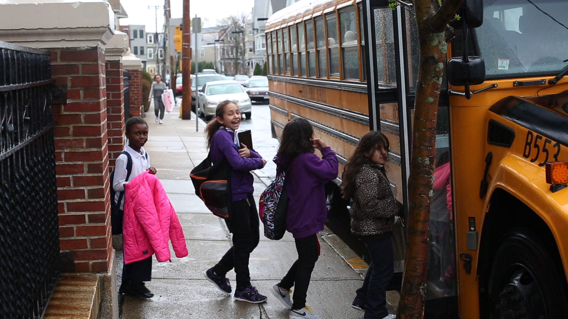 Students boarding school bus from city sidewalk