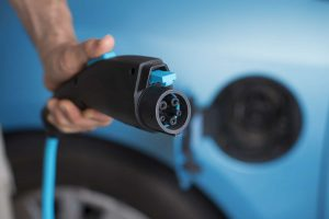 Power plug of electric car -- close up man's hand holding 3 pin power plug of a blue electric car