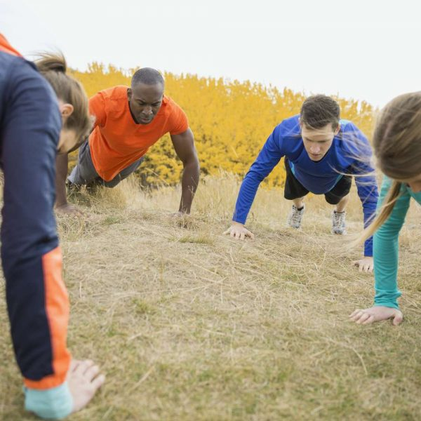 four healthy people doing push-ups outside