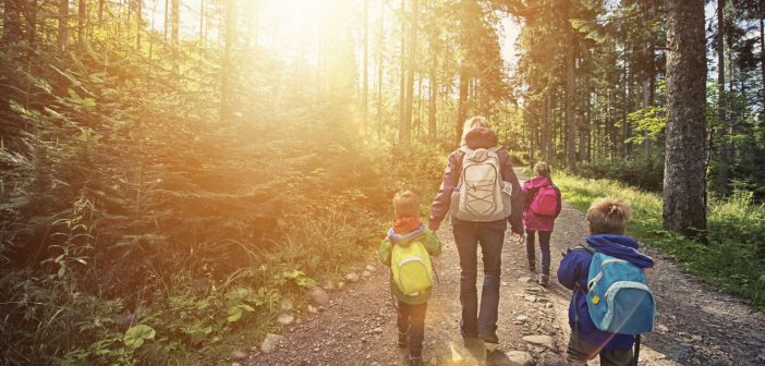 mom and three kids hiking in woods with backpacks