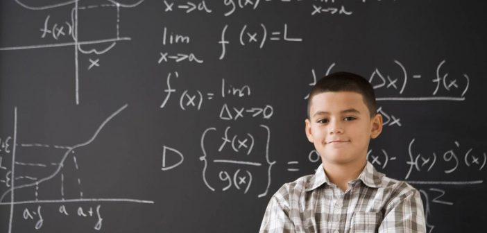 Young man standing in front of chalkboard with statistical functions