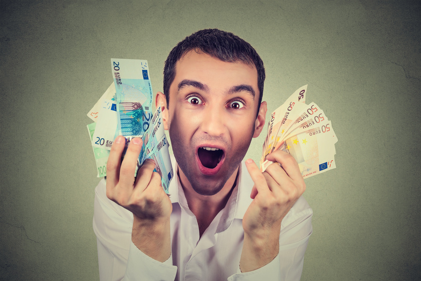 happy young man with money euro banknotes ecstatic celebrates success