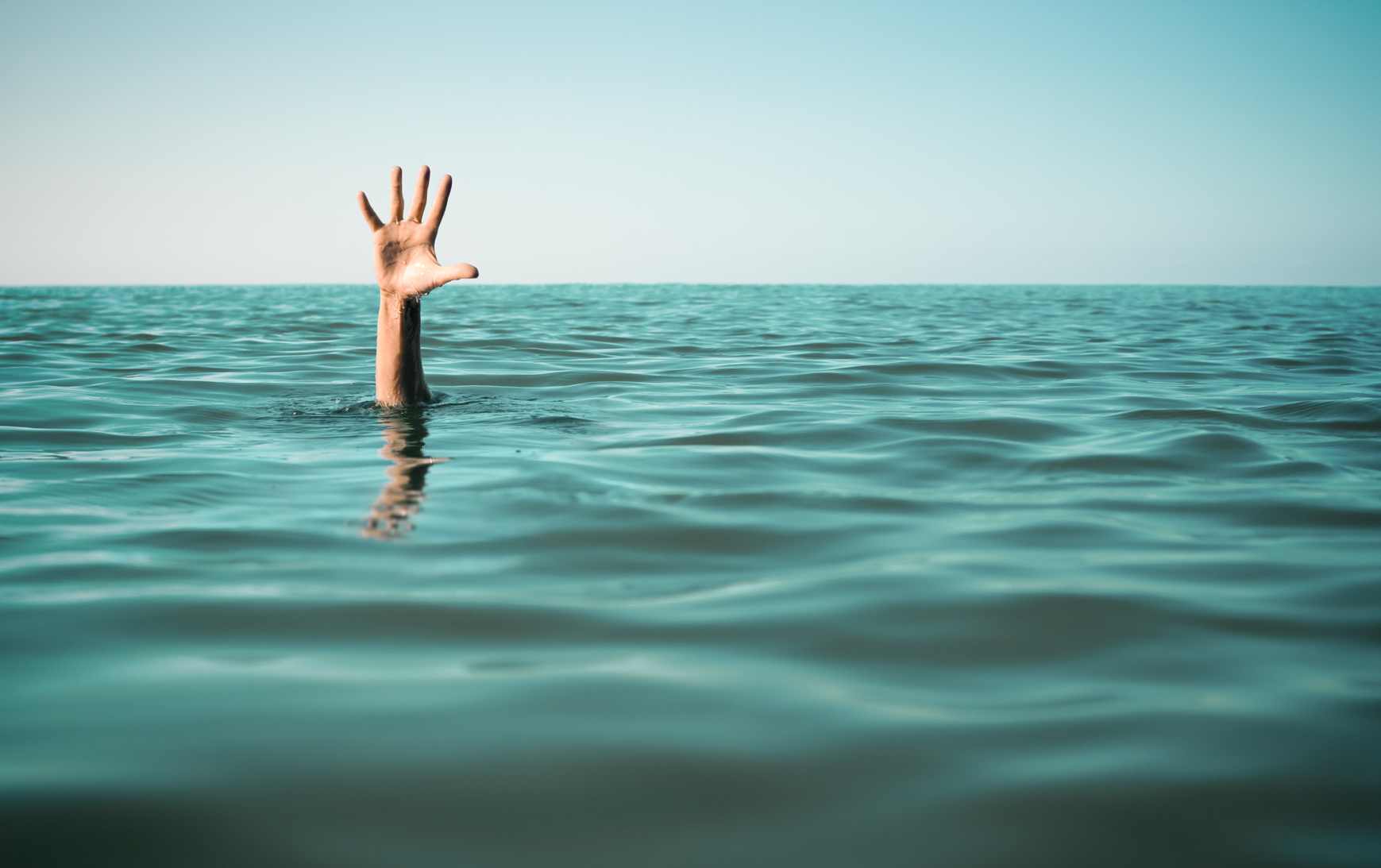 Hand in sea water asking for help.