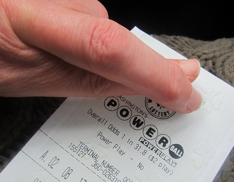 Powerball lottery ticket, and fingers crossed for luck.